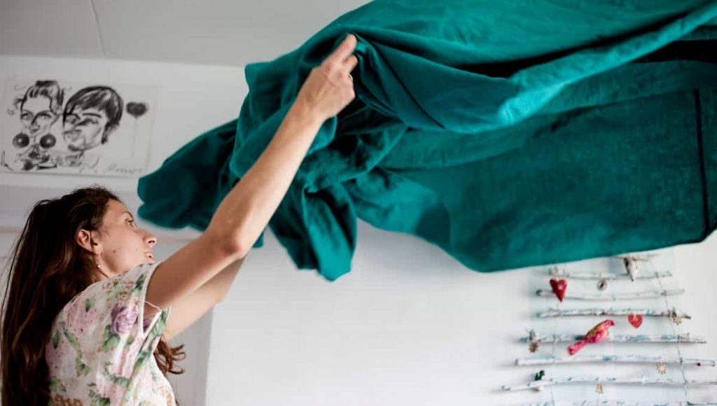 woman changing bed sheets