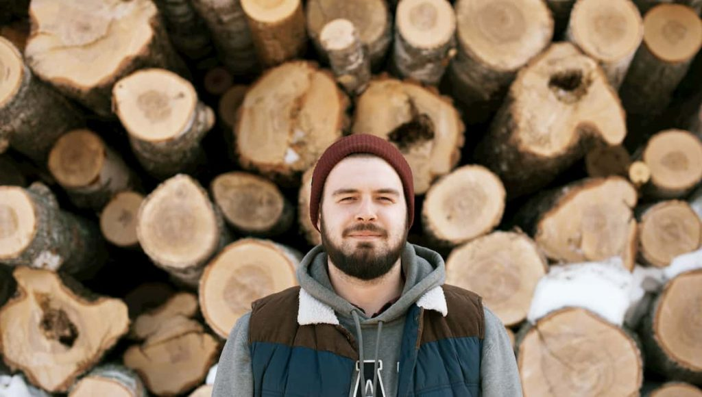 man standing in front of a pile of firewood